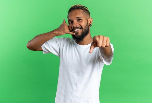 Giovane afroamericano in maglietta bianca che indica con il dito indice alla macchina fotografica che fa mi chiama gesto sorridente amichevole in piedi su sfondo verde