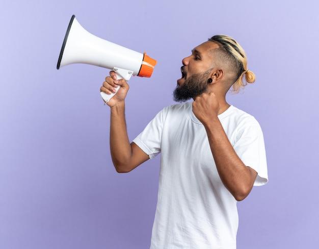Giovane afroamericano in maglietta bianca che grida al megafono felice ed eccitato in piedi sopra il blu