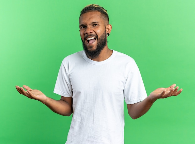 African american young man in white t-shirt shouting with arms raised being angry and displeased standing over green background