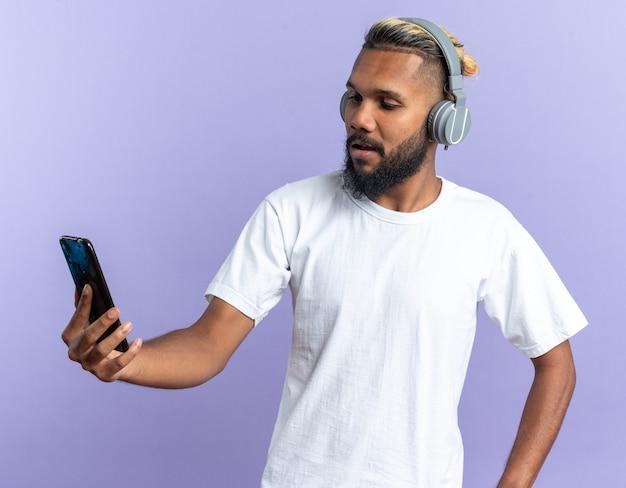 Giovane afroamericano in maglietta bianca con le cuffie che guarda lo schermo del suo smartphone con un sorriso sul viso in piedi su sfondo blu