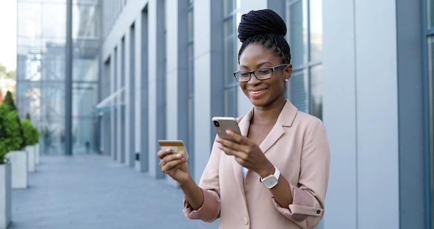 スマートフォン、クレジットカード、オンラインショッピングを使用して眼鏡をかけたアフリカ系アメリカ人の若いきれいな女性。携帯電話をタップしてインターネットで商品を購入する美しい女性実業家。通りのバイヤー。