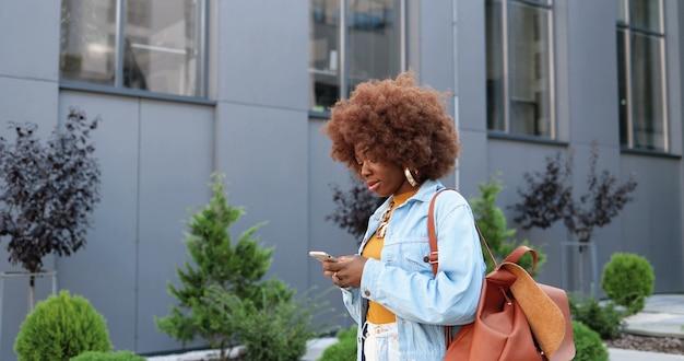スマートフォンでタップまたはスクロールし、街の通りを歩いているアフリカ系アメリカ人の若いスタイリッシュな巻き毛の女性。携帯電話や散歩で美しい女性のテキストメッセージ。外側。メッセージング。