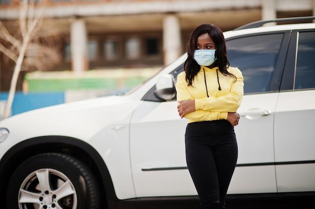 Suv車に対して屋外フェイスマスクを着ているアフリカ系アメリカ人の若いボランティアの女性。コロナウイルスの検疫と世界的なパンデミック。