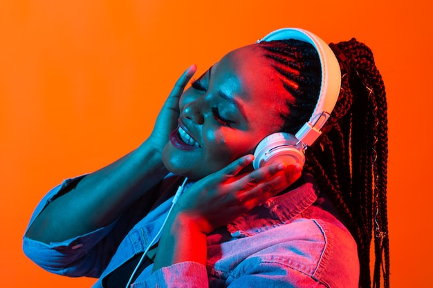 African american young woman listening to music online dancing and singing with headphones