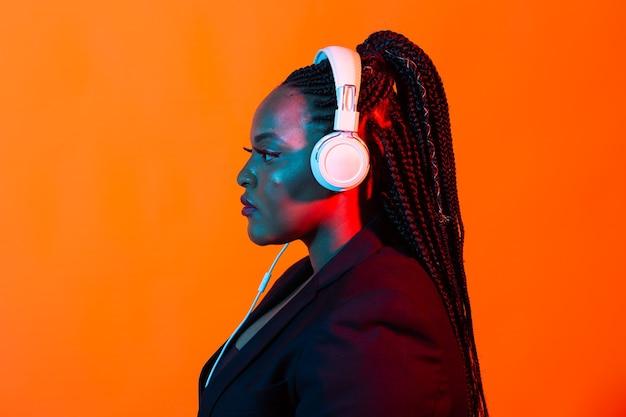 음악 온라인 춤과 헤드폰, 네온으로 노래를 듣고 아프리카 계 미국인 젊은 여자