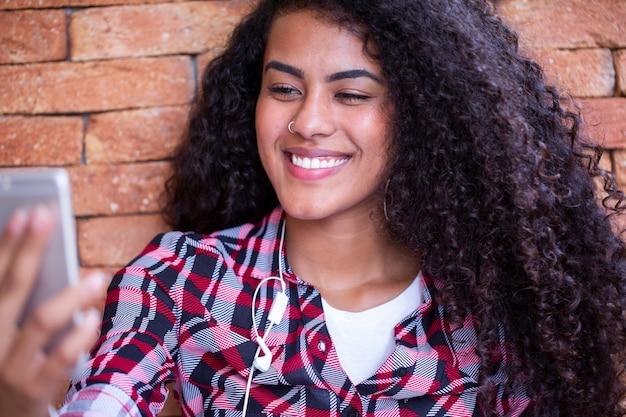 바닥에 앉아 네트워크에서 공유하기 위해 스마트 폰의 전면 카메라에 셀카 사진을 만드는 아프리카 계 미국인 젊은 여자 학생