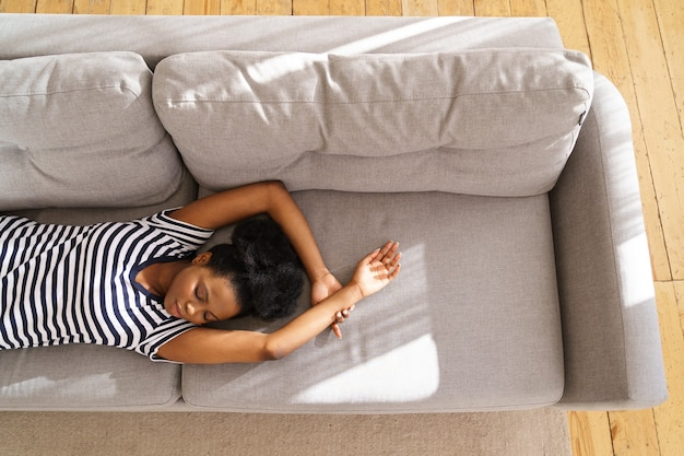 Афро-американская молодая женщина носит раздетую футболку, спит на диване с поднятыми руками у себя дома, закрывает глаза и делает перерыв.
