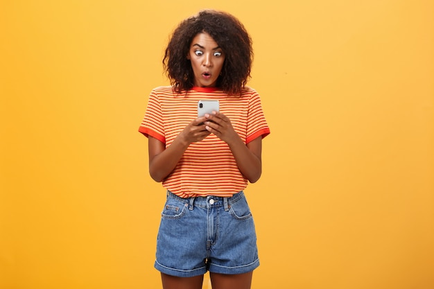 オレンジ色の壁の上のスマートフォンに驚いて興奮して見つめているアフロの髪型を持つアフリカ系アメリカ人の若い女性