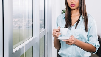 African American young woman with cup near window