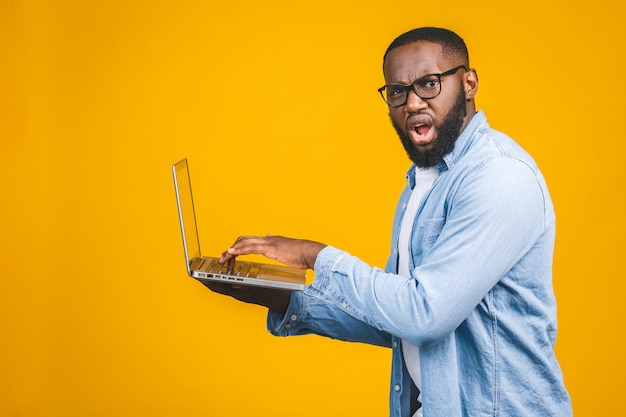 African american ypung man scared a bad news on his laptop, isolated against yellow background.