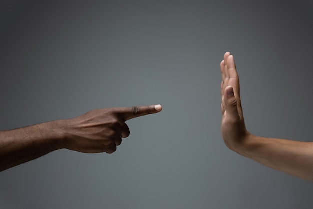 회색 스튜디오 배경에 몸짓으로 아프리카와 백인 손