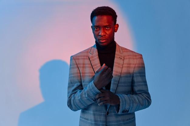 スーツの自信のエレガントなスタイルのネオンの背景にアフリカの外観の男