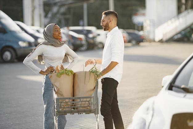 아프리카 아라비아 부부는 전기 자동차 근처에 식료품을 들고 서 있습니다. 전기 주유소에서 전기 자동차 충전