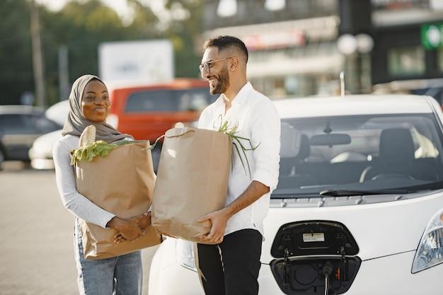 アフリカのアラビア人のカップルが電気自動車の近くに食料品を持って立っています。電気ガソリンスタンドで電気自動車を充電する
