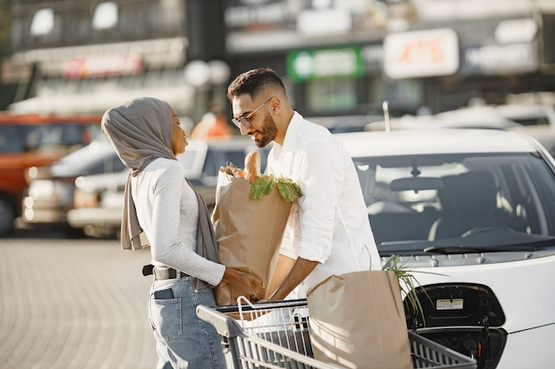 African arabian couple stands with groceries near electric car. charging electric car at the electric gas station