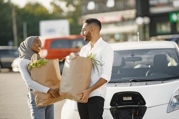 La coppia araba africana sta con generi alimentari vicino all'auto elettrica. ricarica dell'auto elettrica alla stazione di servizio elettrica