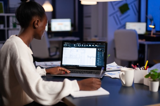 African architect working late at night on laptop with blue prints, looking at graph