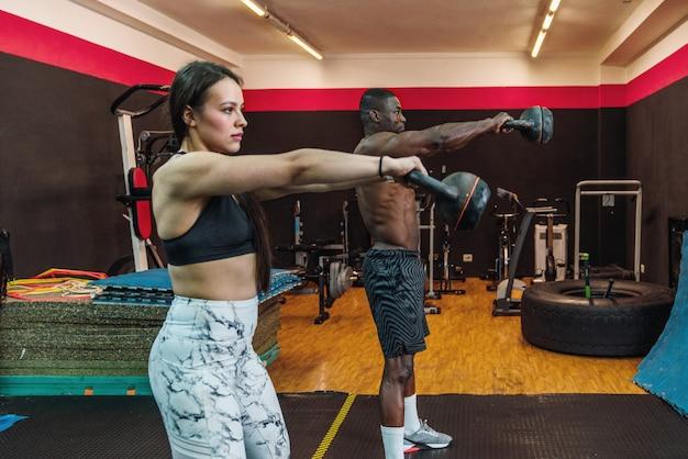 ジムでケトルベルを使って肩の上腕二頭筋と胸筋運動をしているジムのアフリカのアスリートの男の子と白人のアスリートの女の子。 2つの多民族のボディービルダー
