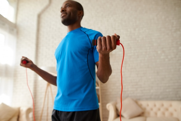 African athlete doing exercises with jumping rope at home.