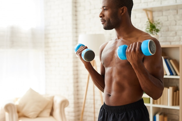 African athlete pumping up muscles by dumbbells.