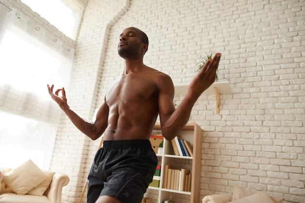 African athlete with bare torso doing yoga pose for balance.