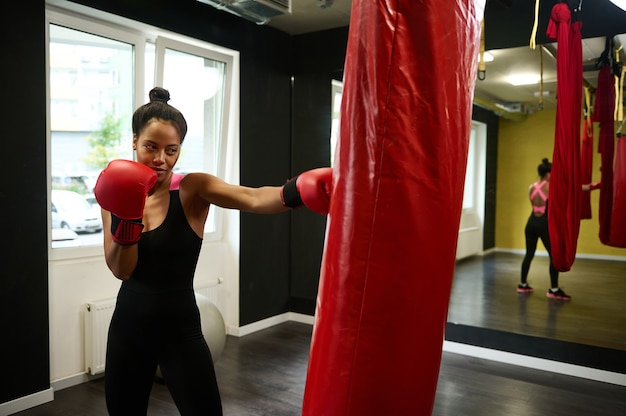 African athlete woman, female boxer with perfect physique wearing red boxing gloves, striking on punching bag in sports gym, with reflection in mirror. martial combat art. healthy active lifestyles