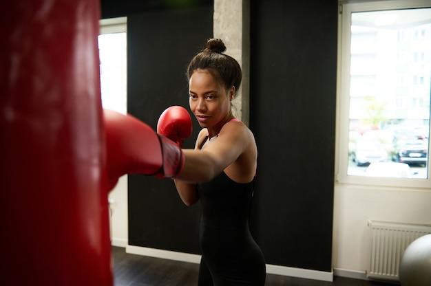 完璧な体格のアフリカの運動女性、赤いボクシンググローブのボクサー、激しく訓練し、まっすぐなパンチを打ち、ボクシングジムで巨大なサンドバッグを打ちます。武道の概念。
