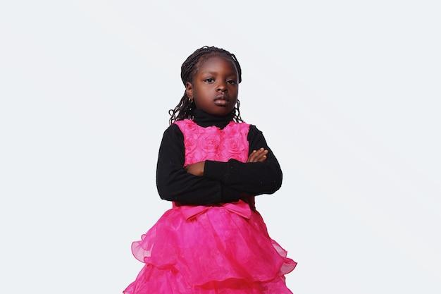 Африканская девочка со сложенными руками выглядит равнодушно
