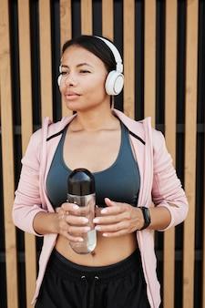 屋外でのトレーニング中に水のボトルを保持しているワイヤレスヘッドフォンでアフリカの美しい女性