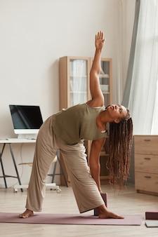 운동 매트에 서서 집에서 거실에서 스트레칭 운동을하는 아프리카 아름다운 여자