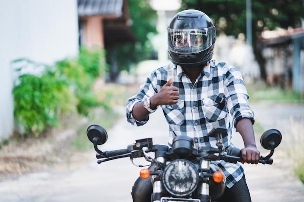 オートバイのヘルメットと眼鏡のアフリカのバイカー