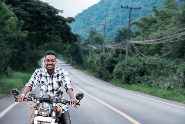 バイクに乗ってヘルメットをかぶったアフリカのバイカーの男が高速道路に乗る