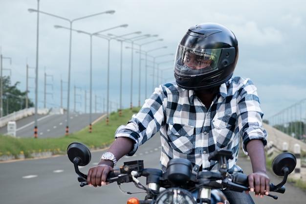 ヘルメットに乗ってアフリカのバイカー男