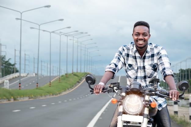 バイクに乗るアフリカのバイカーの男が高速道路に乗る