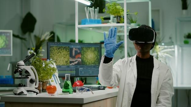 새로운 유전자 실험을 연구하는 가상 현실 헤드셋을 가진 아프리카 생물 연구원