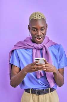 デバイスを備えたアフリカ系黒人男性モデル、スマートフォンの使用、友人とのチャット、メッセージの送信、ニュースの共有、紫色の空間で隔離、彼はショックを受けています