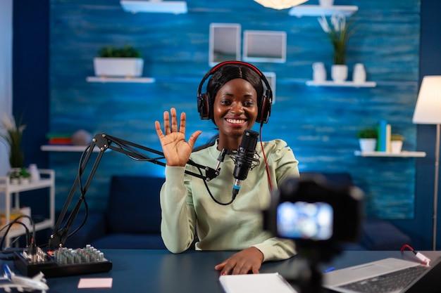 ポッドキャストの撮影中に聴衆に手を振っているアフリカのブロガー。オンエアプロダクションインターネット放送ホストストリーミングライブコンテンツ、デジタルソーシャルメディアの記録