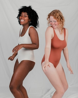 African and blonde young women dancing against grey backdrop