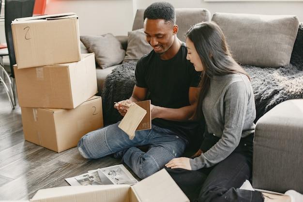 아프리카 소년과 아시아 소녀는 자신의 물건과 함께 상자 근처 거실 바닥에 앉아 있습니다. 부부는 가정용 가구에 대해 생각하고 있습니다.