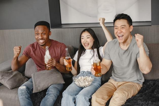 Ragazzo africano e coppia asiatica tintinnano una bottiglia con una birra. amici che guardano la partita di calcio, mangiano popcorn. persone che fanno il tifo per una squadra di calcio.