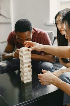 African boy and asian couple playing jenga play board game in a free time