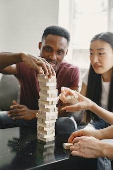 Ragazzo africano e ragazza asiatica che giocano a jenga gioca a un gioco da tavolo nel tempo libero