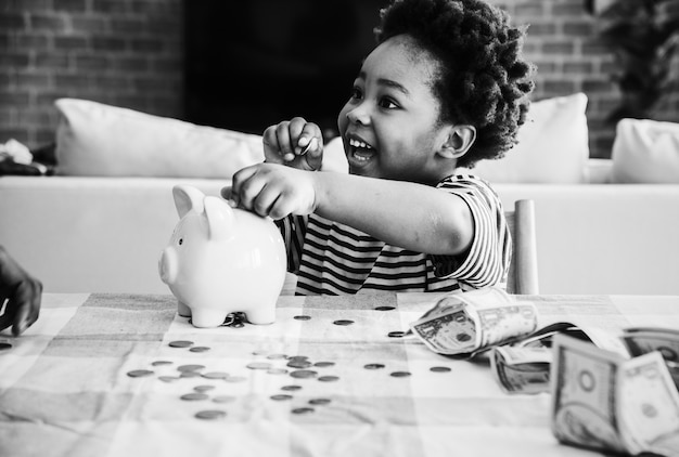 African boy collecting money in a piggy bank