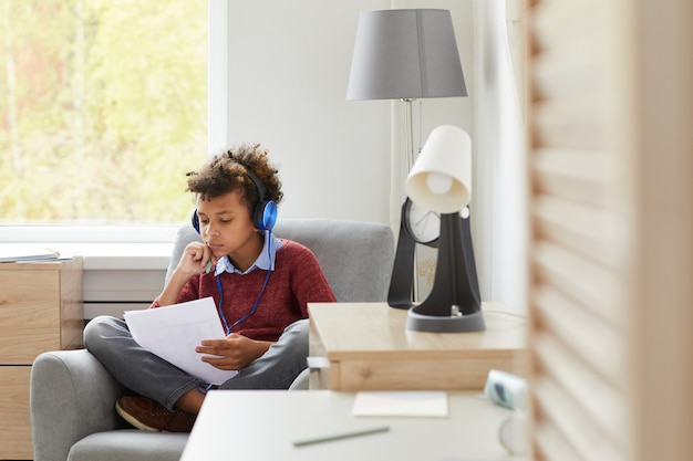 African boy in headphones sitting on armchair with papers he learning lessons or preparing for the exam at home