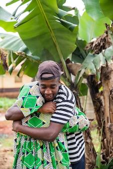 アフリカの少年は祖母を抱きしめ、彼は幸せで、彼らはお互いを愛しています
