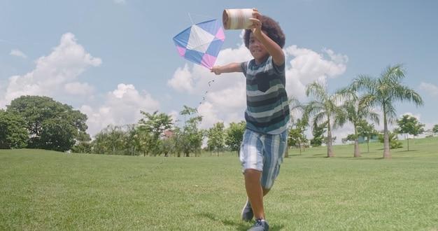 Африканский мальчик пытается запустить воздушного змея в парке. концепция отпускной деятельности.
