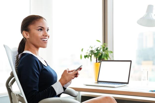 テーブルのそばに座って、オフィスで電話を保持しているドレスを着たアフリカのビジネス女性。