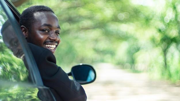 開いたフロントウィンドウで車に座って運転し、笑顔のアフリカのビジネスマン。16:9スタイル