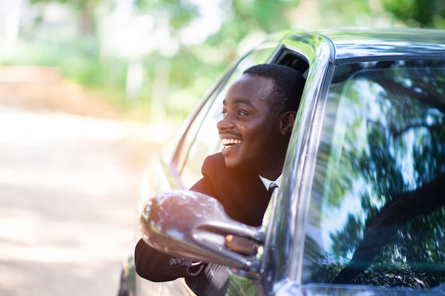 African business man smiling while sitting in a car