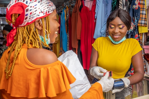African business woman collecting a credit card from a customer
